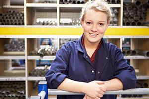 female apprentice in workshop looking at camera