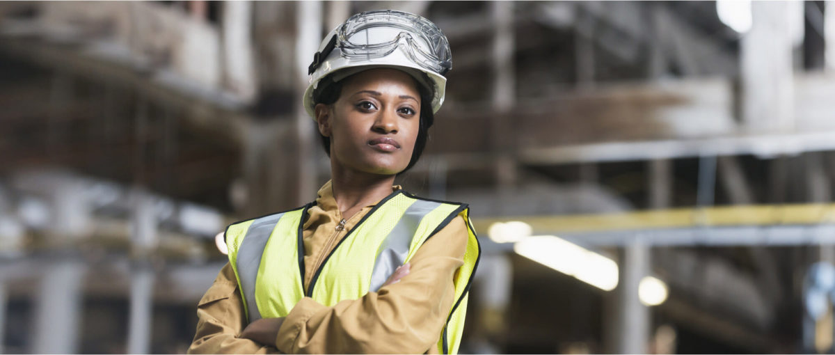 Woman in hard hat and hi-vis stands with folded arms