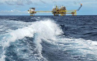 Oil rig out at sea as waves crash in the foreground