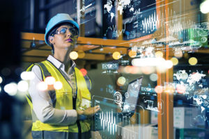 Female engineer in PPE looks at digital displays and lights in workplace