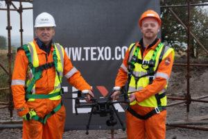 Conal Ferguson holding a drone alongside trainer Ian Cameron from Texo Compliance