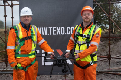 Conal Ferguson holding a drone alongside trainer Ian Cameronl from Texo Compliance