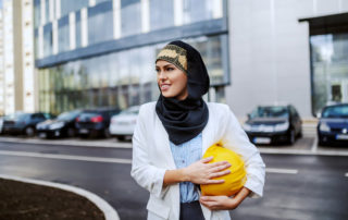 Middle eastern woman wearing headscarf holds yellow hard hat ready for work