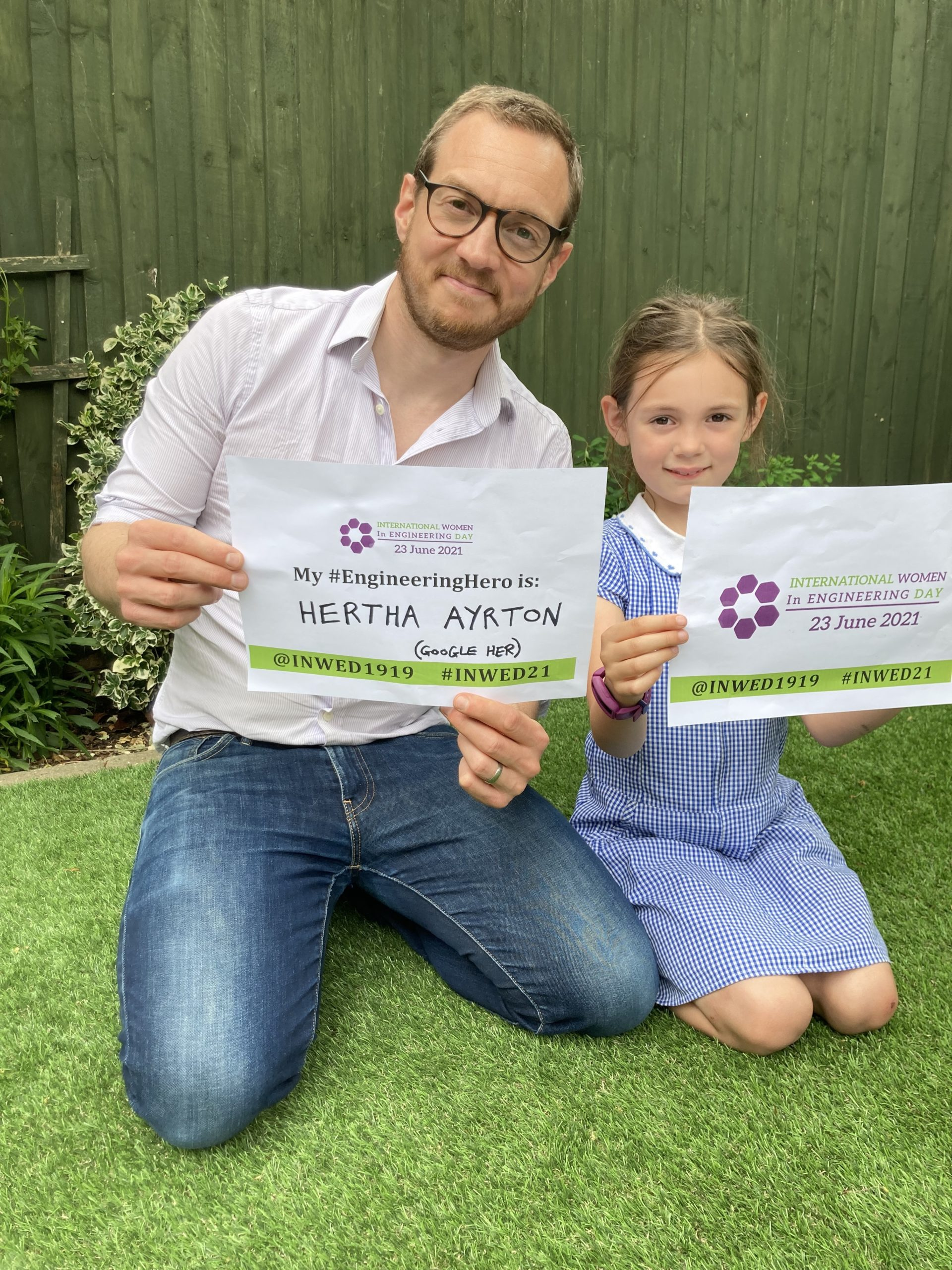 Photo of Mat Parker and his daughter holding signs to celebrate International Women In Engineering Day